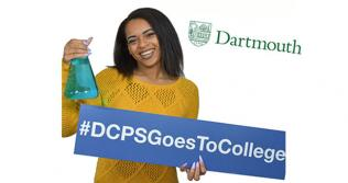 DCPS graduate holding a chemistry flask