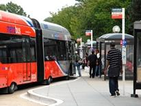 Bus Stop Change Service Request - red and grey double-length bus pulling up to a bus stop