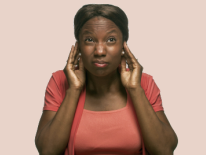 Woman with hands next to her ears