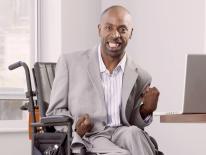 Man in a wheelchair at a computer