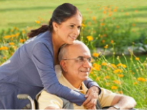 Woman helping man in wheel chair in garden