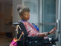 Woman in a power chair presses the accessible door opener